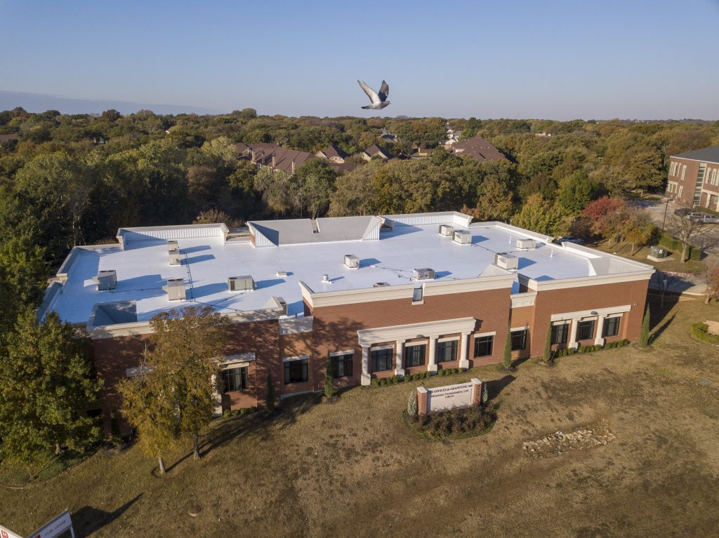Commercial building in Fort Worth, TX with freshly installed white TPO commercial roof and bird flying overhead